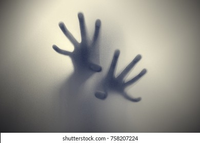 shadow of hand behind frosted glass
