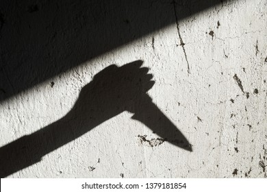 Shadow of the hand holding a big sharp knife. Murderer, killer or robber with a knife. Criminal. Crime. Horror scene.