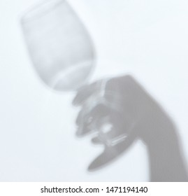 Shadow of hand holding glass on white wall background