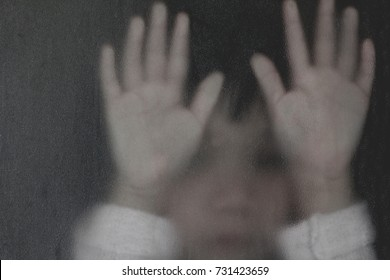 Shadow hands of the little girl behind frosted glass representing dangerous, fear, help, horror and scary.Abstract blurry image.Concept of violence and exploited children.And for Halloween background.