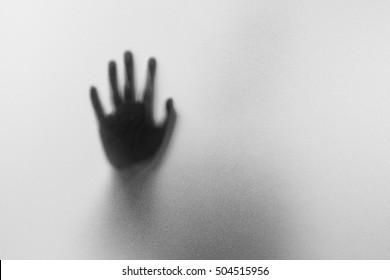 Shadow hands of the Man behind frosted glass.Blurry hand abstraction.Halloween background.Black and white picture