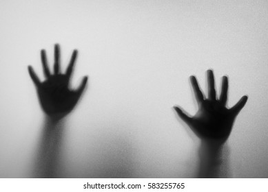 Shadow hands of the Man behind frosted glass.Blurry hand abstraction.Halloween background.Black and white picture.Blur picture.