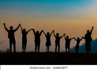 The shadow of a happy family holding hands in the meadow during sunset Happy family enjoying life together outdoors Round dance celebration ceremony