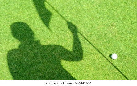 shadow of helper assistance holding golf flag hole