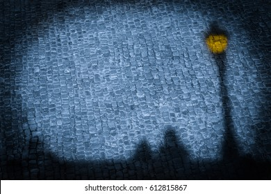 Shadow image nostalgic silhouettes of couple and illuminated lamppost in spotlight on cobblestone road background at night (copy space)/Nightly Street Theater Scenery