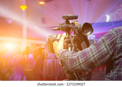 Shadow image,Video camera operators are currently working with video cameras.Producers are recording videos for a scene in the making of the movie on a Background light blur of nightclub