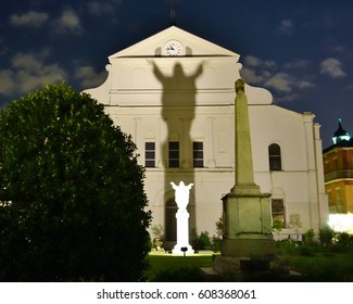 The shadow of Jesus Christ from a statue of Him on the back of St. Louis Cathedral in the French Quarter of New Orleans, Louisiana early evening with blue partly cloudy sky to end a nice spring day.