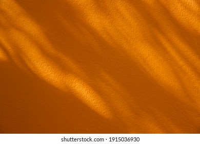 shadow of leaves on yellow concrete wall background