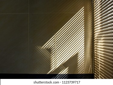 Shadow and light through blinds window on tiled wall. Abstract form morning light and shadow on the wall.