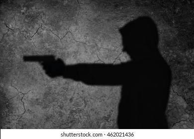 shadow man is aiming with gun
