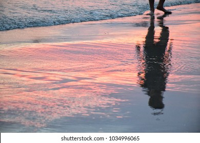 shadow of man in beautiful light sunset at the shoreline - Shutterstock ID 1034996065