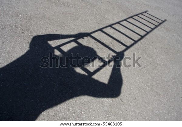 Shadow of man climbing ladder on asphalt