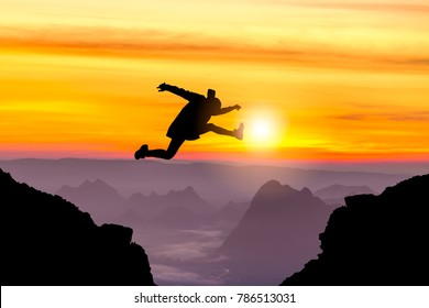 Shadow Man jumping on top of a mountain with a background morning light / advanced concepts in business.