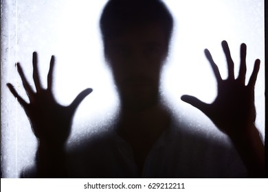 Shadow of a man leaning against glass wall