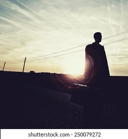 shadow man on empty road in sunset,lonely traveler , freedom concept,outsider,change life ,freedom of choice
