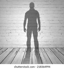 Shadow of a man on white brick wall and wooden floor, abstract square interior background