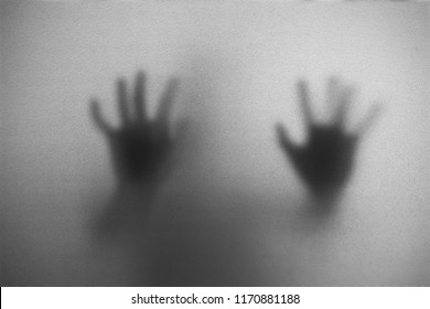 Shadow of man on the white frosted glass representing dangerous, fear, help, haunting, horror and scary.