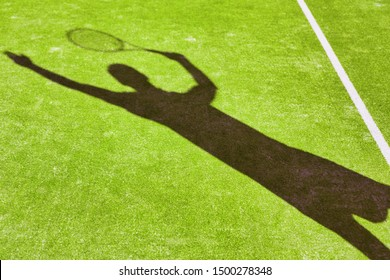 Shadow of a man playing tennis in green court