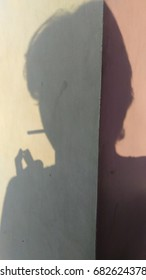 shadow of a man smoke.on a surface wall.