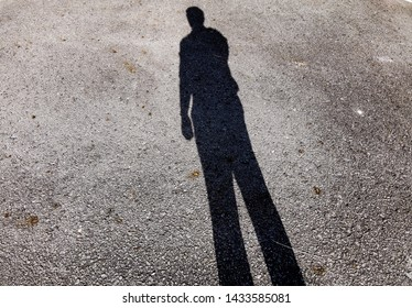 Shadow of a man standing alone. A man looking at his shadow when the sun was behind him