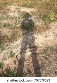 Shadow of a man standing and wearing a hat.