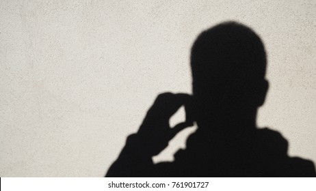 shadow of man talking on the phone projected on white wall