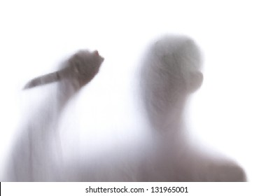 Shadow of men standing behind frosted glass and holding a knife