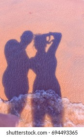shadow men and women on the sand