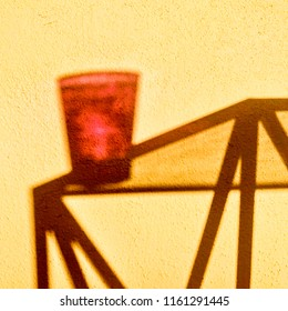 shadow of a metal glass topped table and red glass on a magnolia yellow painted wall