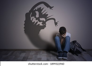Shadow of monster on wall and scared boy in room