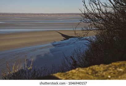 Shadow of Mont-Saint-Michel Abbey looming on water and sand.