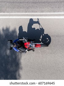 The shadow of a motorcyclist on the asphalt road. Top view