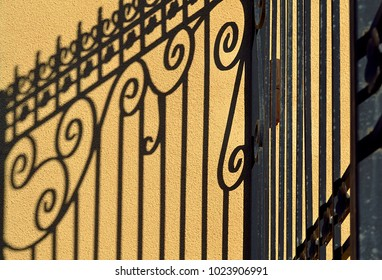 A shadow on an orange wall from a vintage metal fence. Backgrounds and textures.