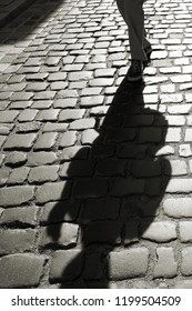 Shadow of oncoming people on cobblestones in backlight