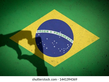 Shadow of patriotic hands making heart shape in front of a Brazilian flag painted on concrete wall background
