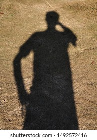 Shadow of people on dry grass