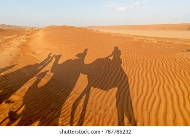 Shadow of people riding on camels during the golden hours at the desert dune of Wahiba Sands, Oman. Sand ripples in the foreground.