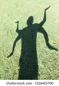 A Shadow person with 4 arms standing over the green grass