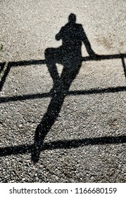 Shadow of a person balancing on one leg on a rail  reflected on a gravel ground