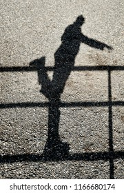 Shadow of a person balancing on one leg on a fence reflected on a gravel ground
