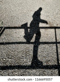 Shadow of a person balancing on one leg while hopping on a fence reflected on a gravel ground