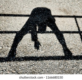Shadow of a person balancing on a rail while bending over looking through their legs and reaching for the ground reflected on a gravel ground