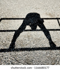 Shadow of a person balancing on a rail while bending over looking through their legs reflected on a gravel ground