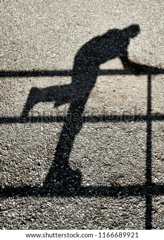 Shadow of a person climbing a fence