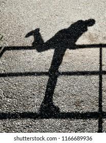 Shadow of a person climbing over a fence reflected on a gravel ground