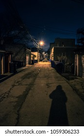 Shadow of a Person in a Dark City Alley at Night