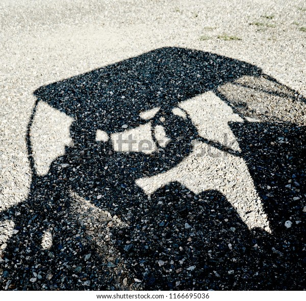 Shadow of a person driving a golf cart  reflected on a gravel ground
