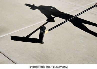 Shadow of a Person holding a broom while sweeping a cement slab
