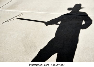 Shadow of a Person holding a metal rake reflected on a cement slab