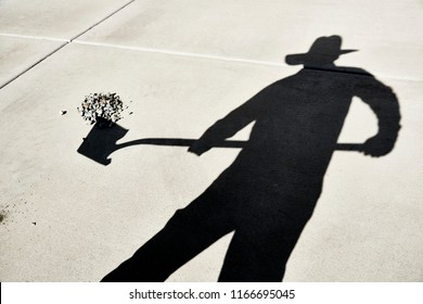Shadow of a Person holding a shovel to shovel gravel reflected on a cement slab